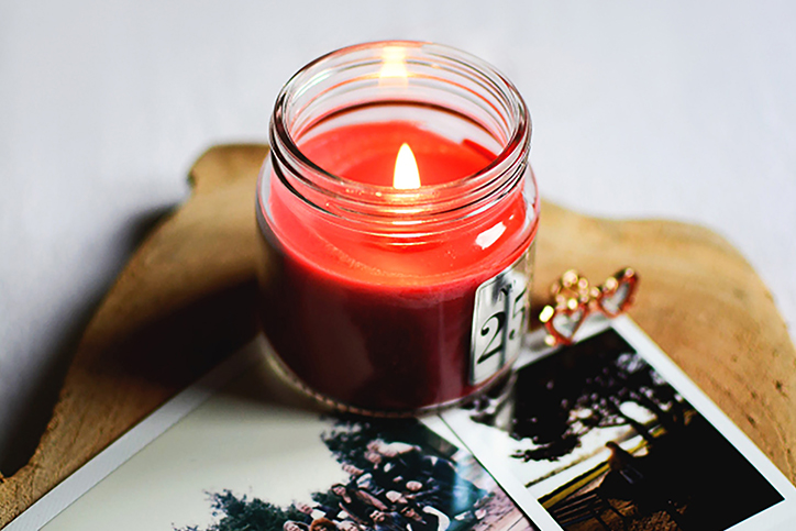 A red candle lit next to some photographs