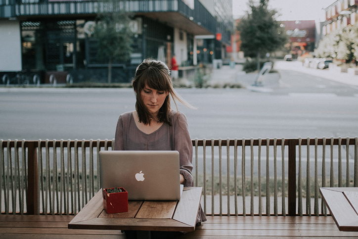 A woman outdoors typing on a laptop
