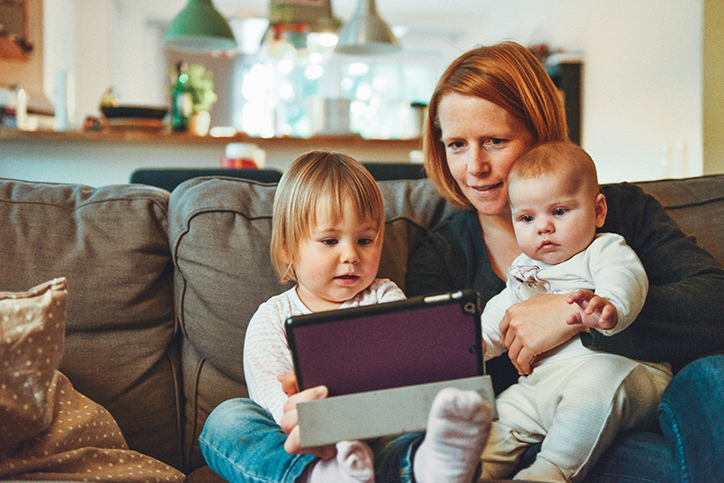 A mom and her two kids looking at a tablet