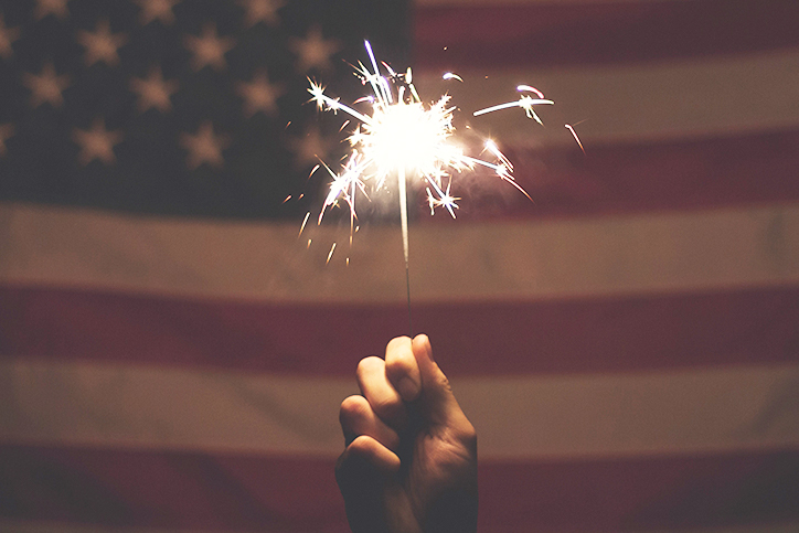 Someone holding a sparkler in front of an American flag
