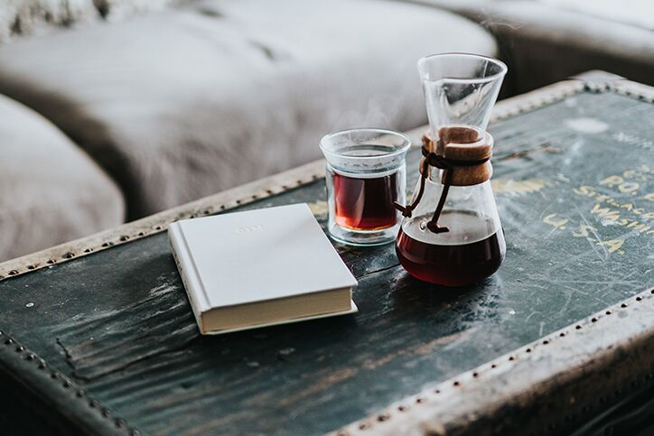 A decanter and cup of coffee next to a book