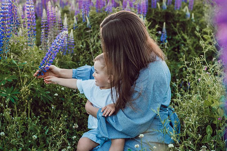A mother and child picking purple flowers