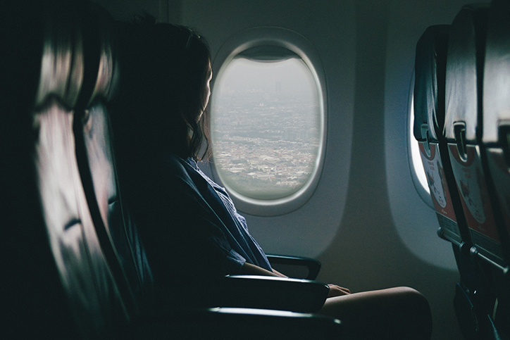 A woman staring out a plane window