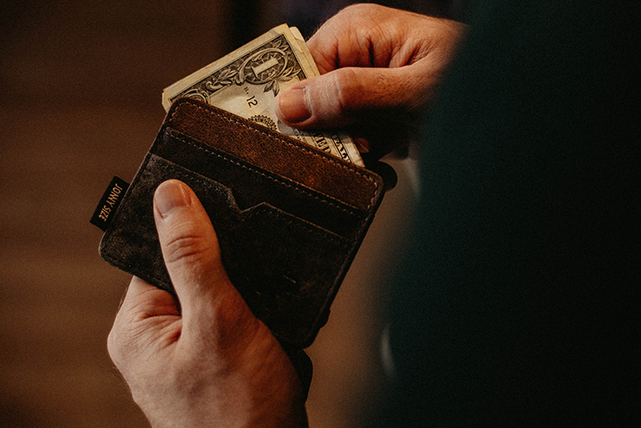 A man pulling cash out of a wallet
