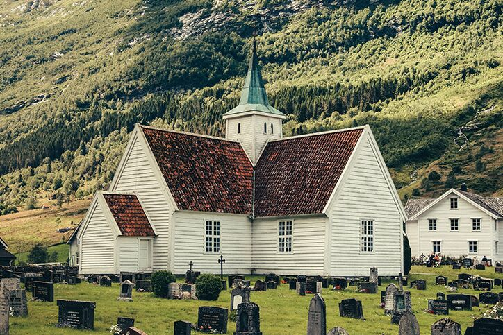 A church and a graveyard with rolling hills in the background