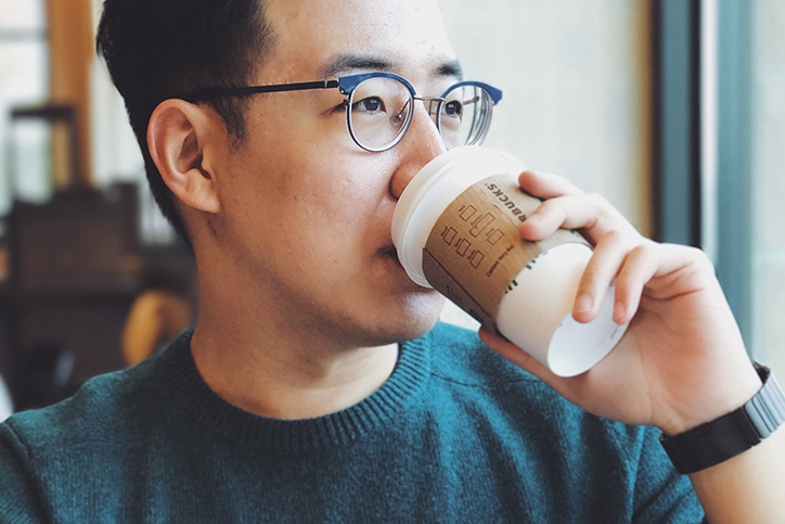 A man drinking a cup of coffee