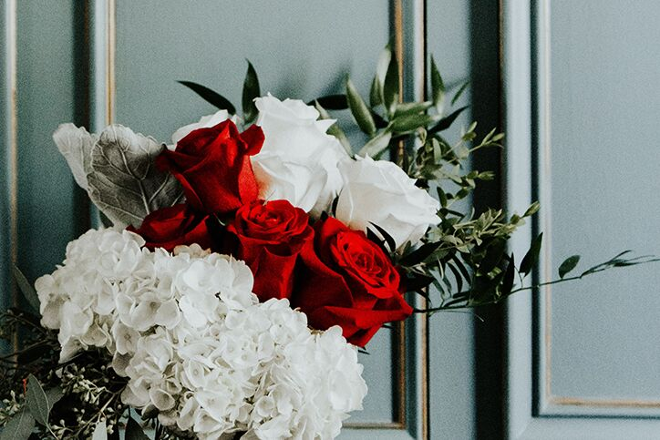 Red And White Flowers Against A Teal Door
