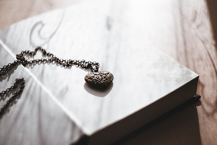 A metal locket laying on a book
