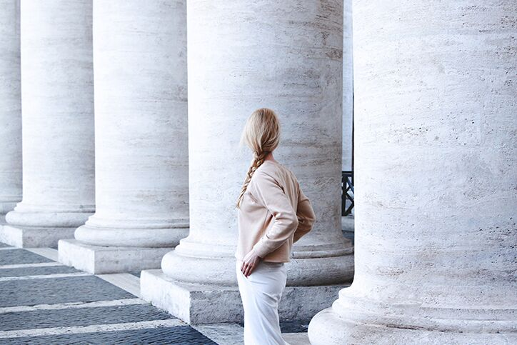 A woman standing next to large marble pillars