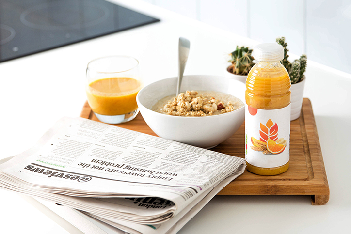A bowl of oatmeal next to some orange juice and a newspaper