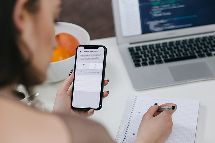 a woman looking at her smartphone and writing a list