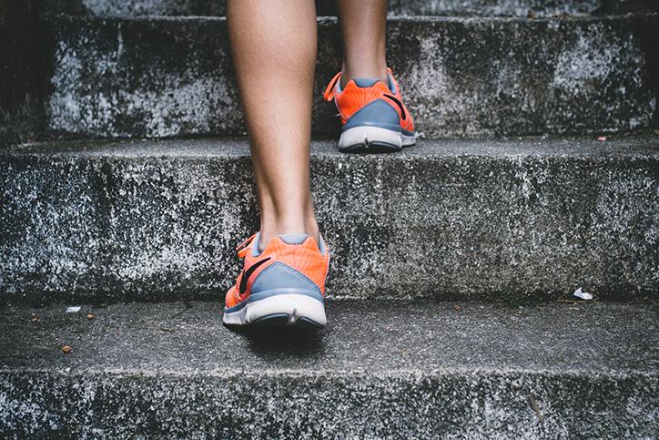 A woman in workout shoes going up concrete steps