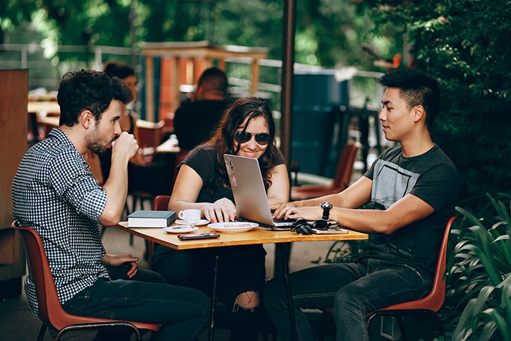 Three friends sitting at a cafe on a laptop