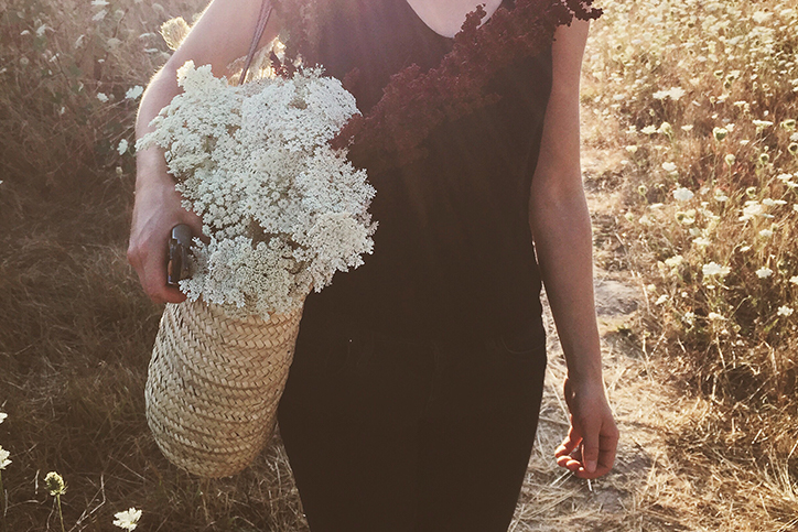 A woman carrying a basket of flowers
