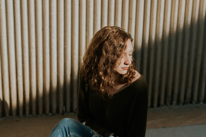 A woman sitting in front of a concrete wall