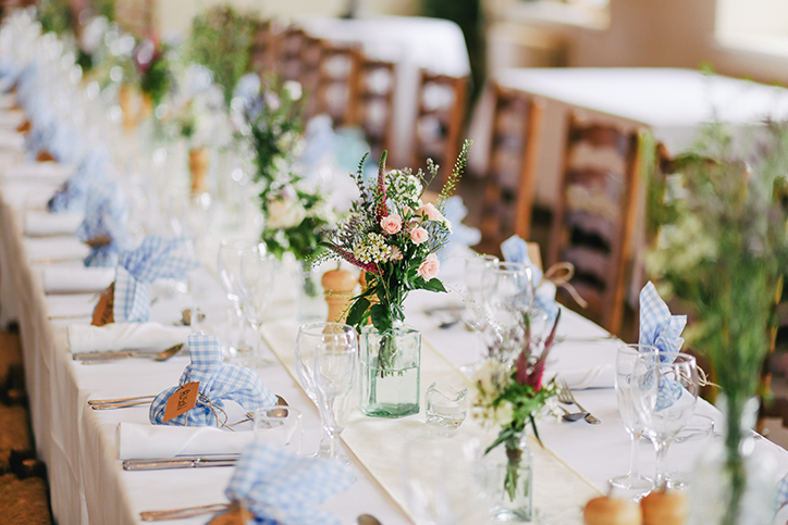 A long table set with dinnerware and flowers