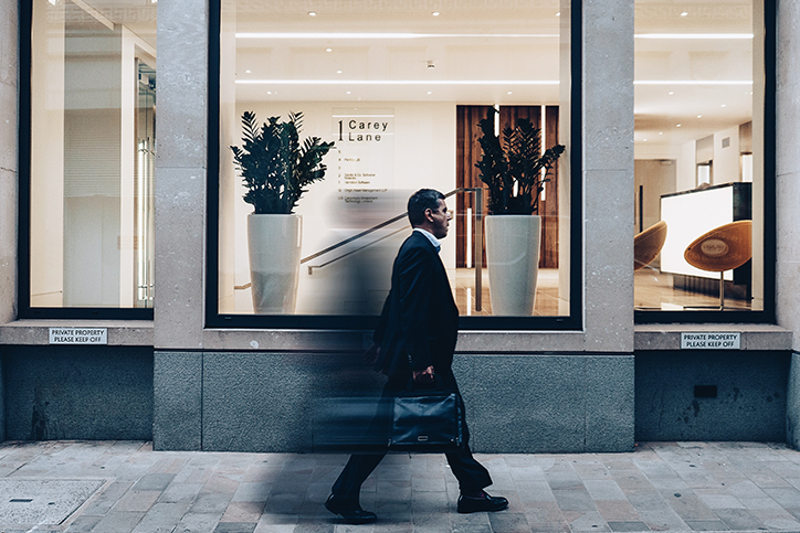 A man in a suit walking past a building