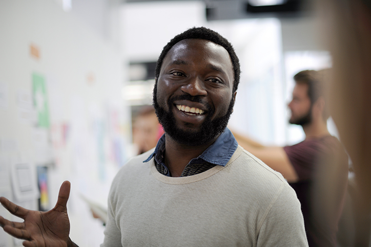 A man smiling next to a whiteboard