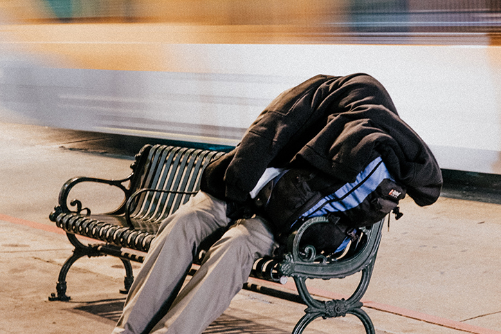 A homeless person asleep on a bench
