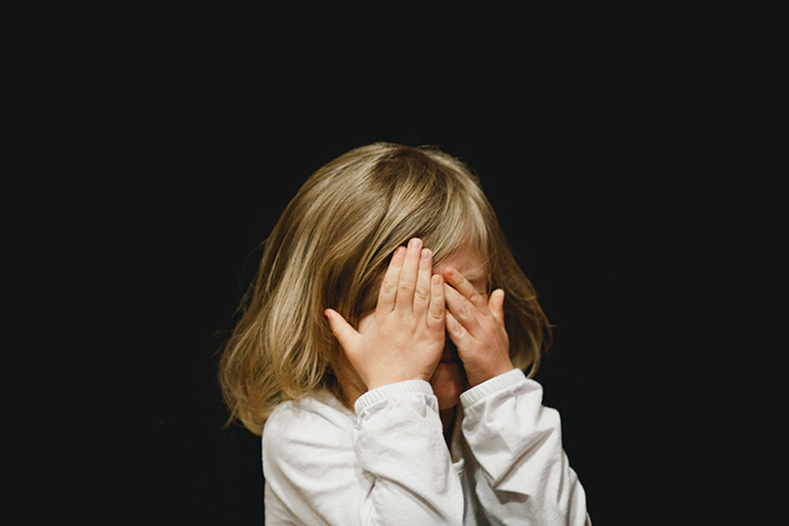 A little girl covering her face