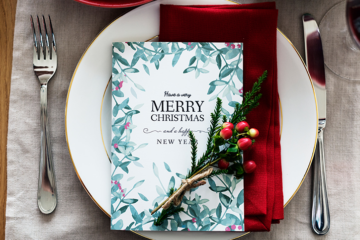A card reading Merry Christmas set atop a plate and napkin
