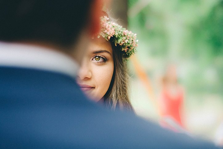 A bride looking over the shoulder of her groom