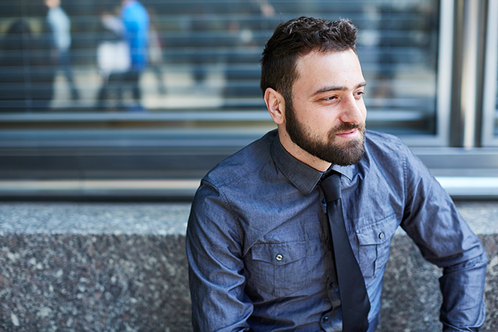 A man in a button-up shirt and tie sitting outside