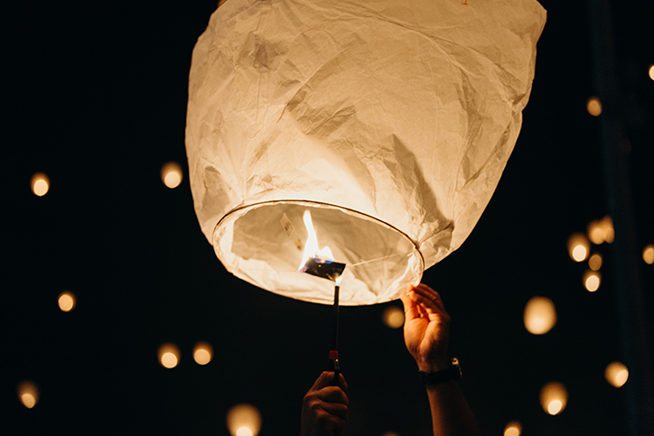 Someone lights a paper lantern and waits to release it