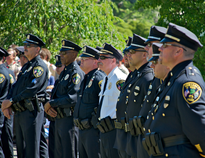 Police Officers stand at a memorial service.