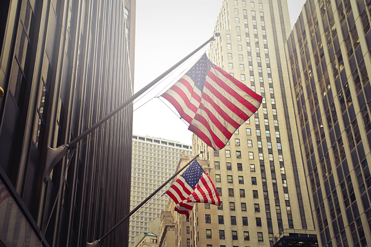 Two American flags on flagpoles on a building downtown