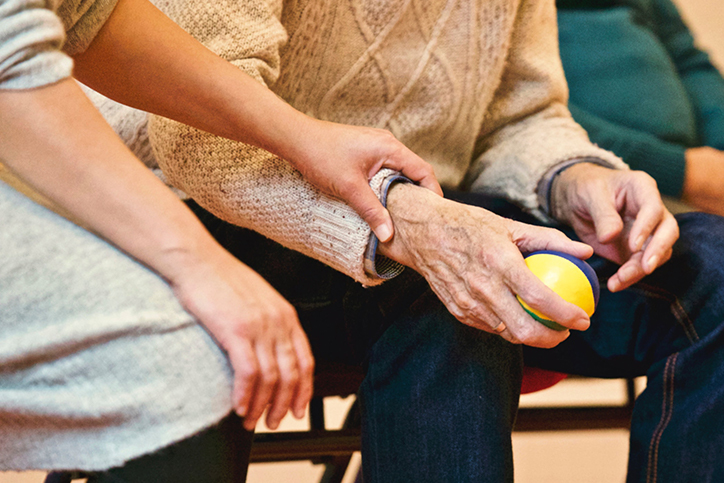 An older man holding a ball and working on physical therapy