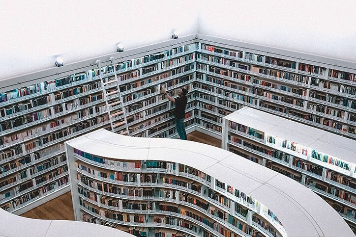 Shelves of books and a person looking at them