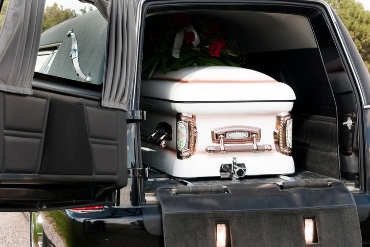 A casket sits in the back of a hearse