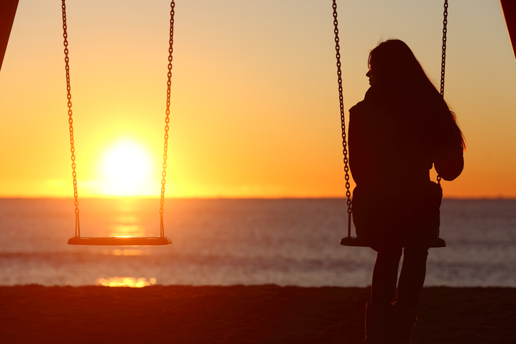 woman sitting alone on swing