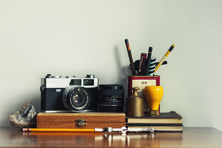 A shelf with books, pencils, and a camera