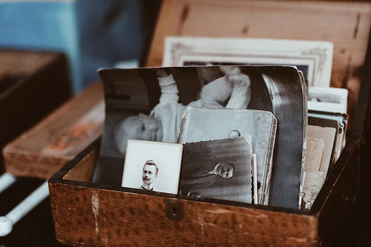 A box of old family photos sitting in a storage box.