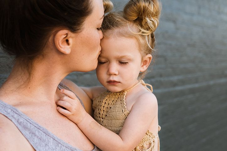 A mother kisses her daughter on the forehead
