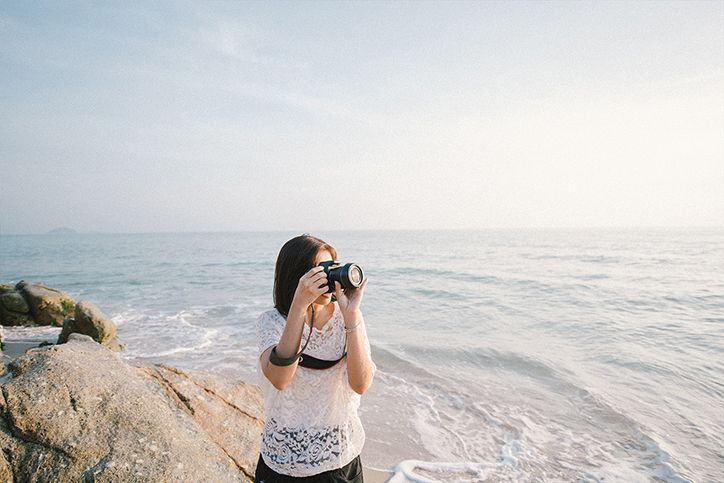A woman taking pictures at the beach