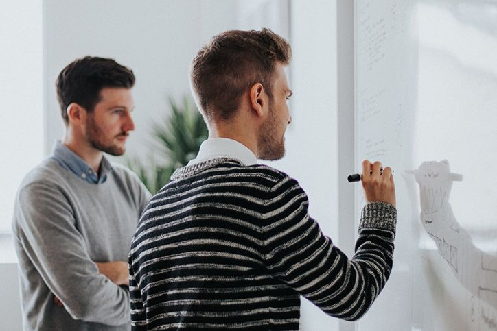 Two men write their marketing plans on a whiteboard.