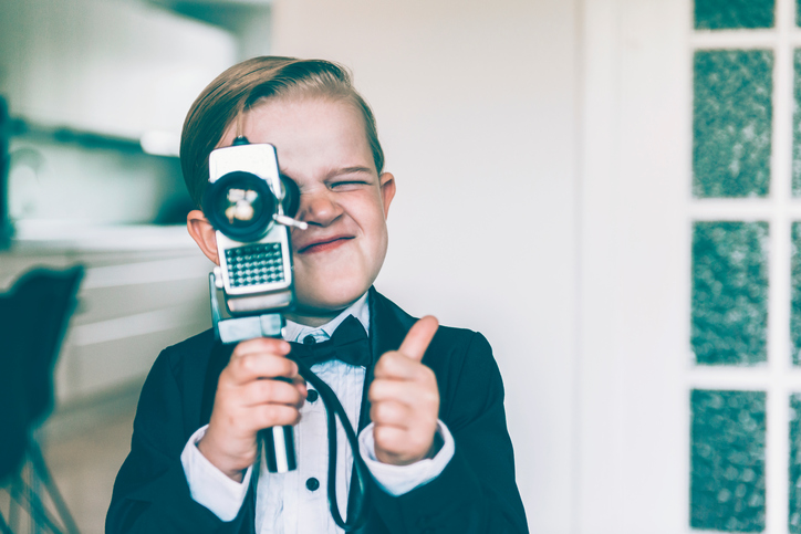 A kid holding a video camera holds a thumbs up