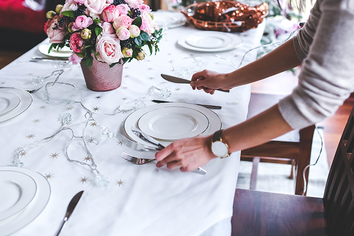 A woman setting the table for a funeral home's event