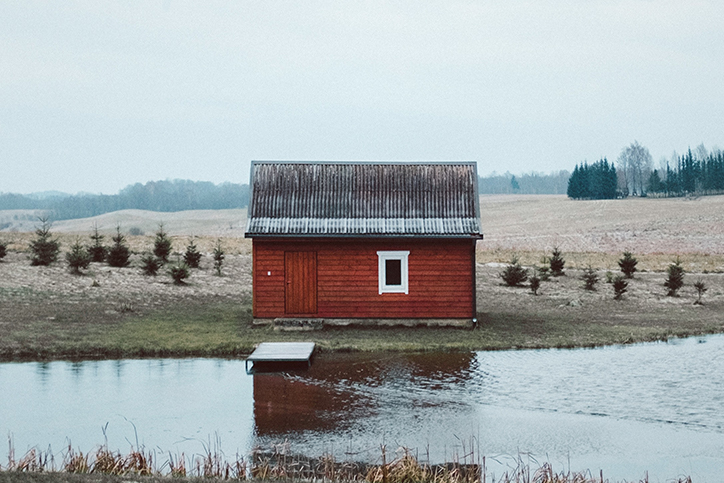 A red shed next to a pond