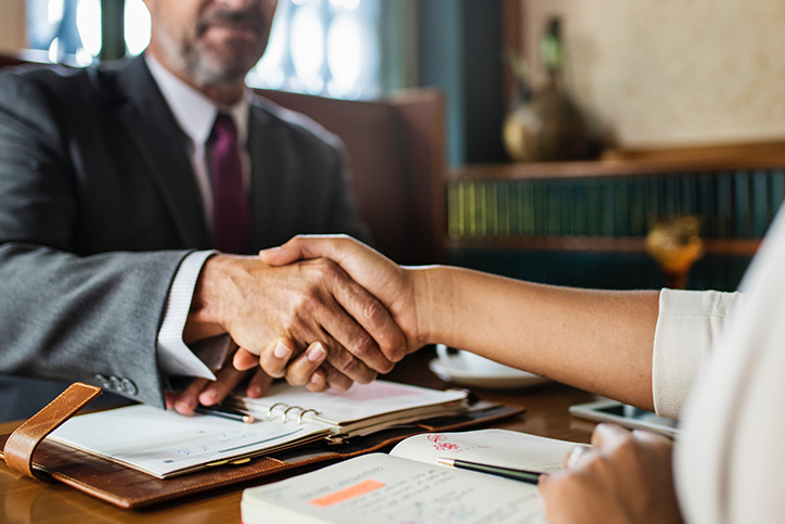 Two people shake hands at a business desk.