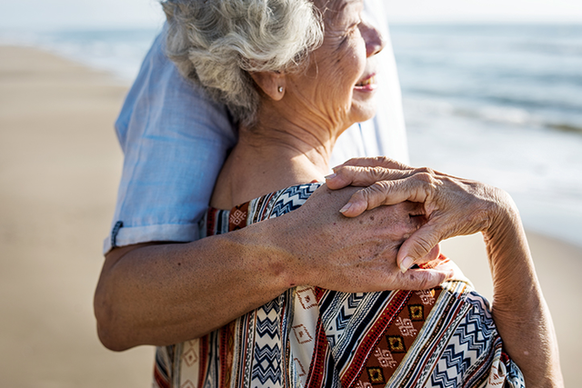 an old couple holding hands on the beach