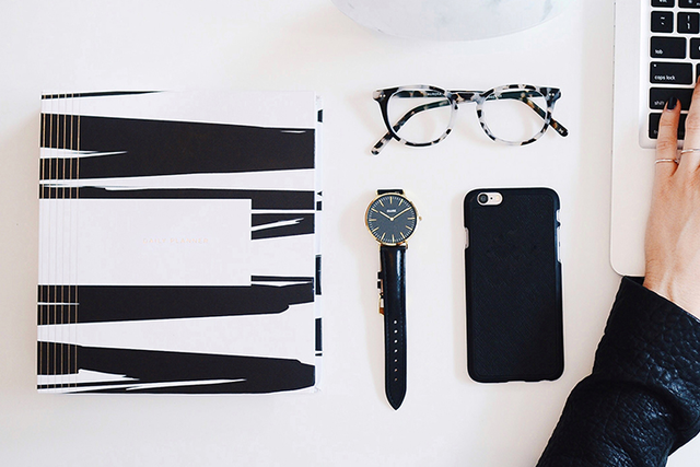 phone, notebook, glasses and watch, sit on a desk