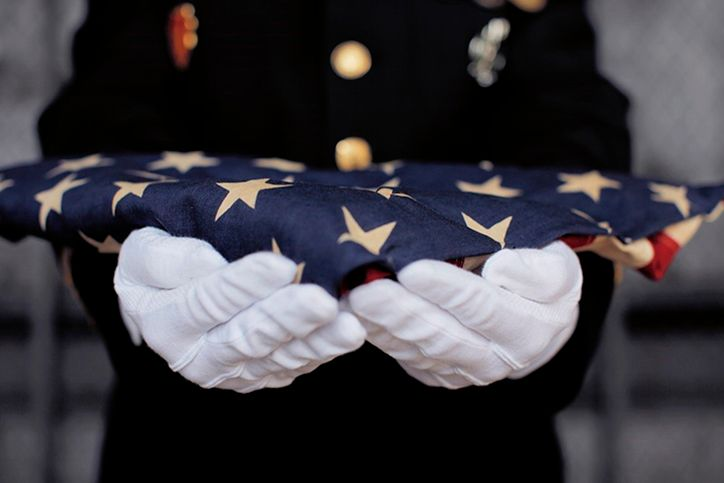 A military member presenting a folded American flag
