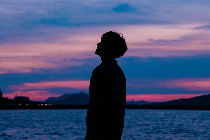 A man's silhouette in front of a sunset