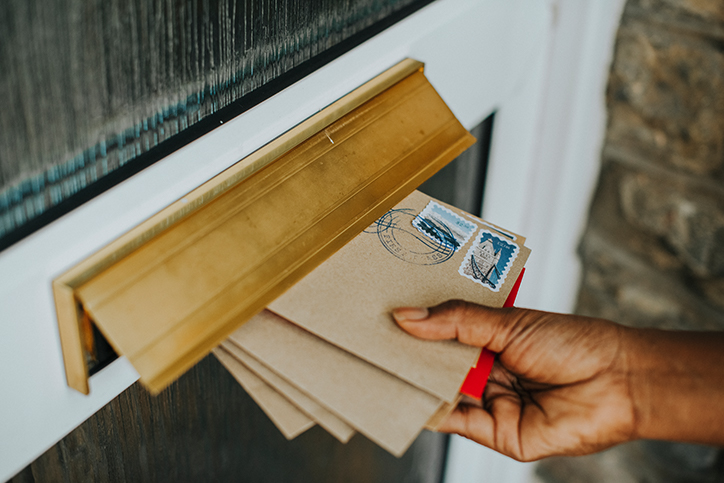 hands placing letters in mail slot