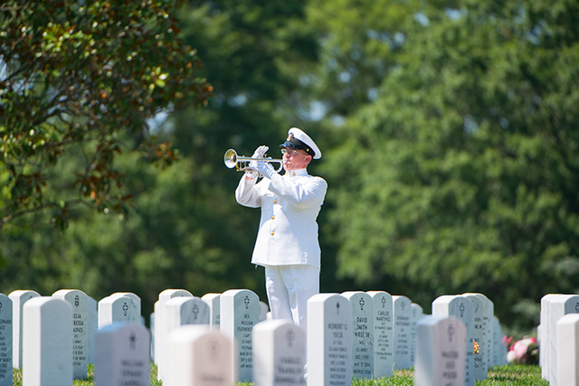 military man playing bugle