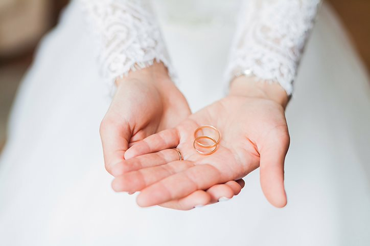 Bride holding wedding rings